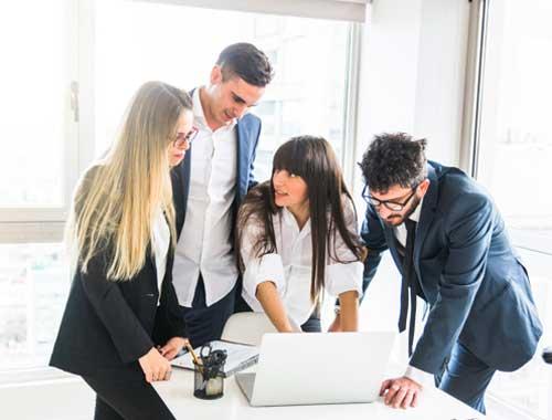 grupo-empresarios-en-la oficina-mirando-portatil