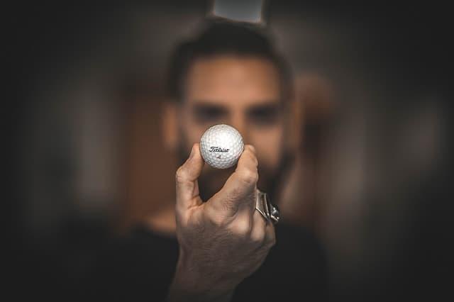 mano y bola de golf